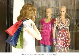 a shopper looking at two mannequins in a shop window